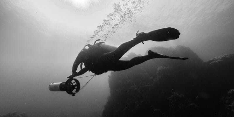 scuba diver underwater with sea scooter black and white photo