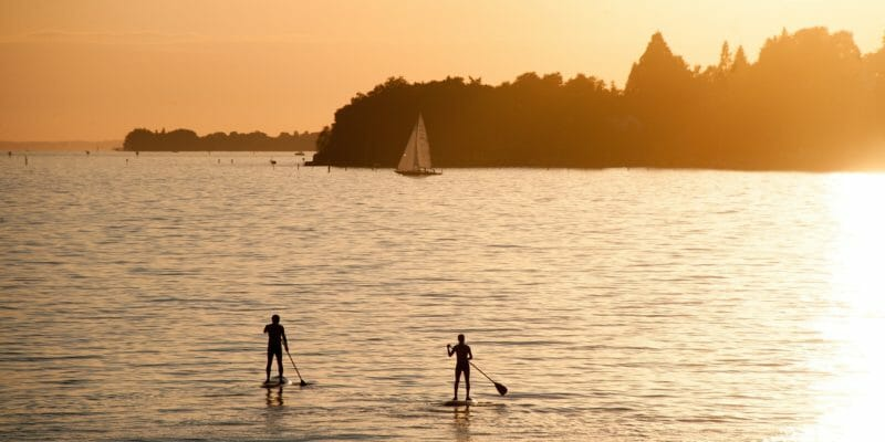 two people on stand up paddleboards in the sunset
