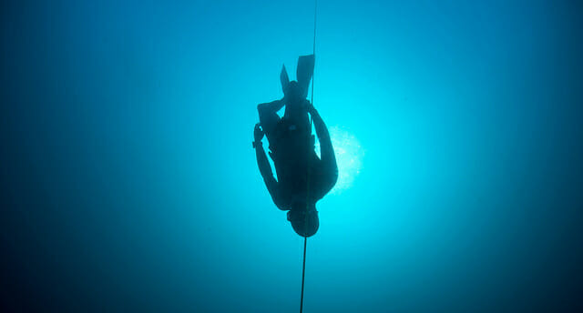 freediver descending in clear blue water