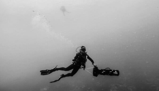 scuba diver with sea scooter underwater black and white