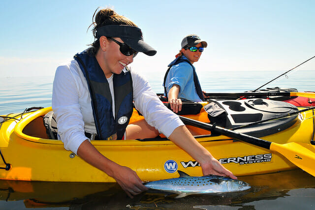 woman kayak fishing holding spanish mackerel