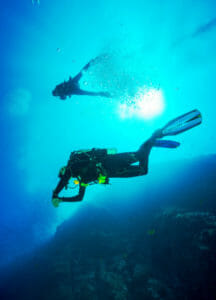two scuba diving buddy's diving underwater in clear conditions divers safety