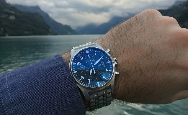 man's hand with stainless steel wristwatch in front of water and mountains