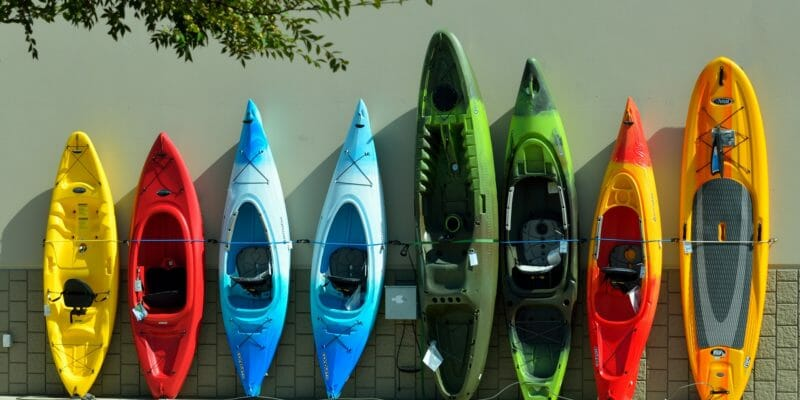 eight colorful kayaks leaned up against a wall