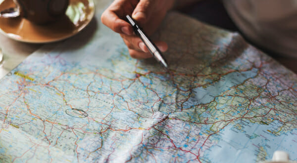 person examining map with pen and coffee
