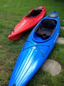blue and red recreational sit-in kayaks on land