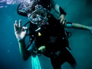 scuba diver and guide making OK hand sign divers safety