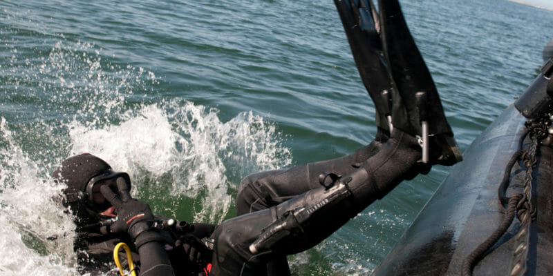 us navy diver diving into the water backward from rubber dinghy