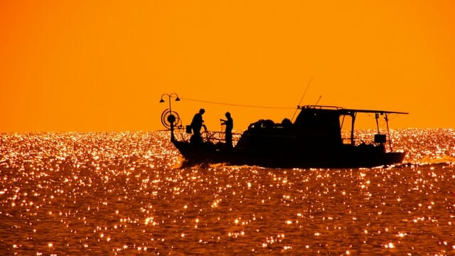 fishing boat in the sun silhouette