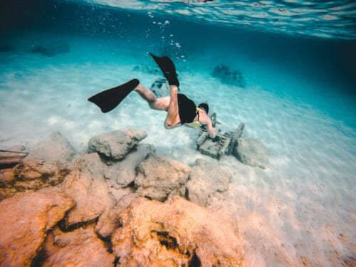 freediver in shallow water above rocks