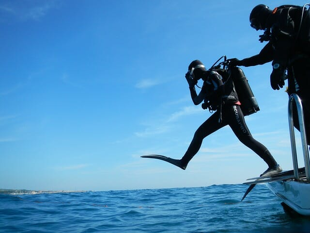 scuba diver entering the water with giant stride entry