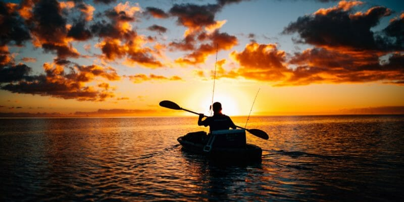man kayak fishing at dusk