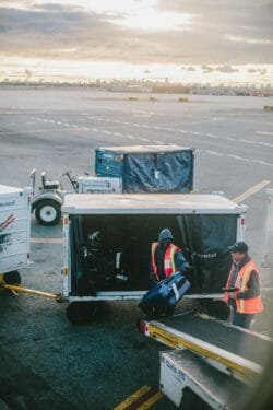 airline baggage handler loading bags on airplane