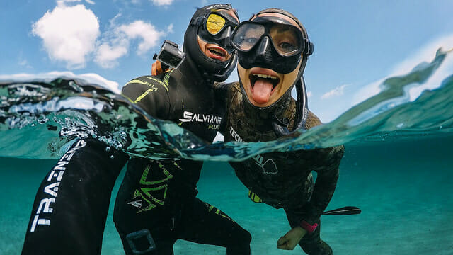two freedivers posing for photo with freediving masks and wetsuits