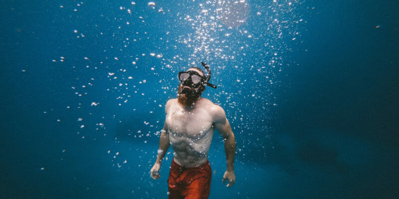 freediver underwater with mask ascending