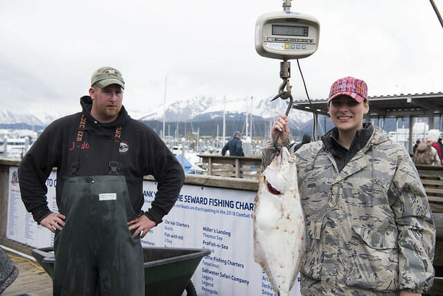 man and woman standing on dock and weighing large fish on scale