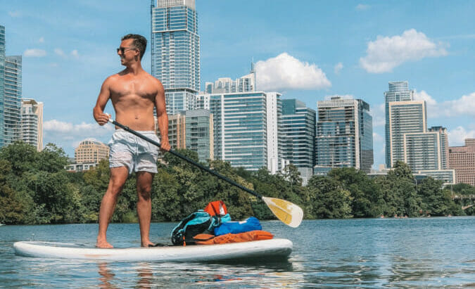 man on stand up paddleboard with dry bags