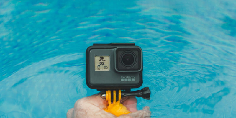 man holding gopro with handle in water