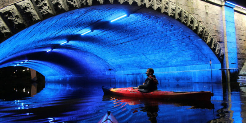 man in kayak under bridge at night lights