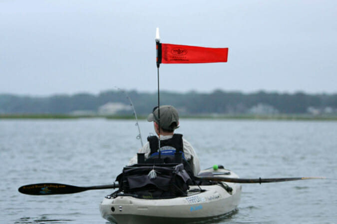 kayak angler on kayak flying a high viz kayak flag and light