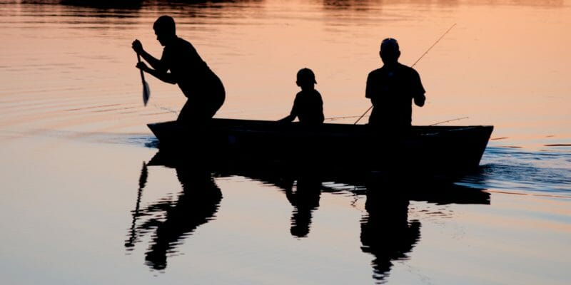 three people fishing from canoe at dusk