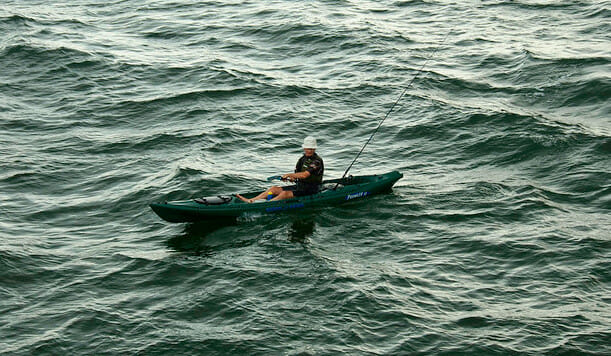 man on sea kayak with fishing rod