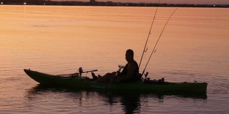 kayak angler at dusk with fishing rods