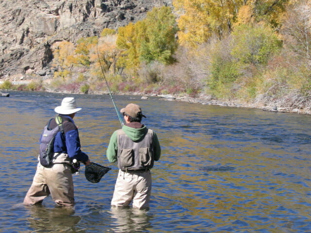 two men fly fishing for salmon in river