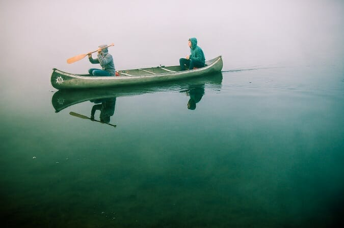 two men in canoe on calm lake