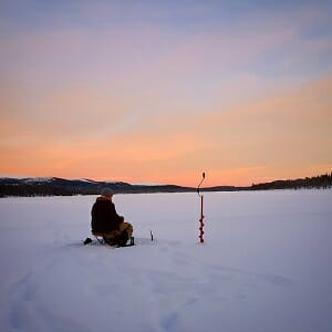 ice angler sitting on ice sunset with hand augers