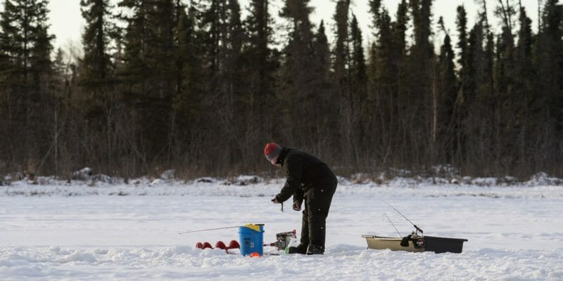 man ice fishing with auger and sledbucket and
