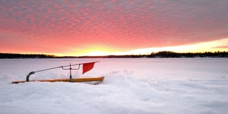 ice fishing tip up and sunset