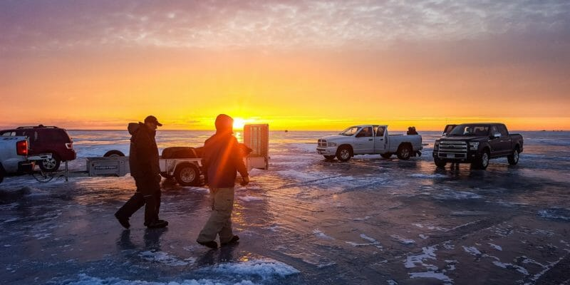 ice fishing on frozen lake with pick up trucks