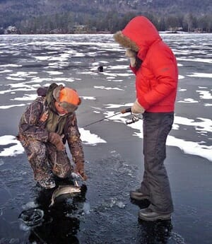 two ice anglers pulling fish from hole