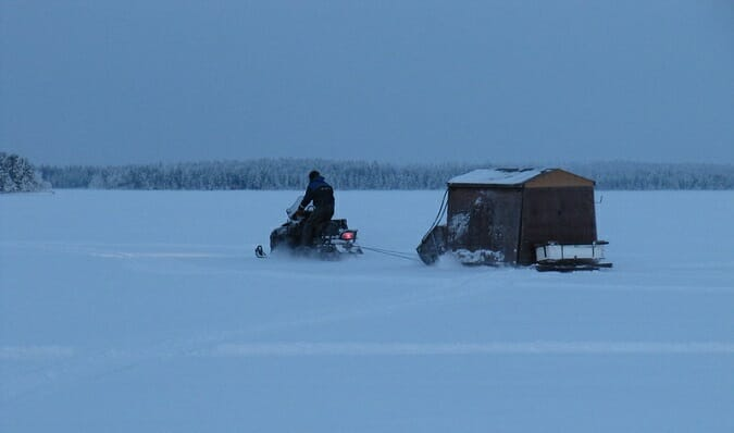 ice angler on snowmobile towing shelter