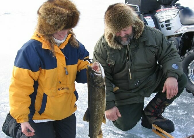 man and woman wearing fur hats ice fishing with pike
