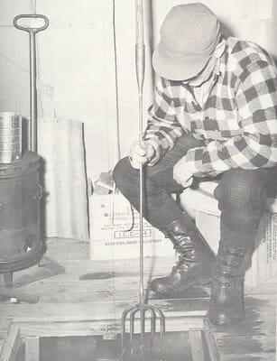 black and white photo of ice fisherman with spear in darkhouse