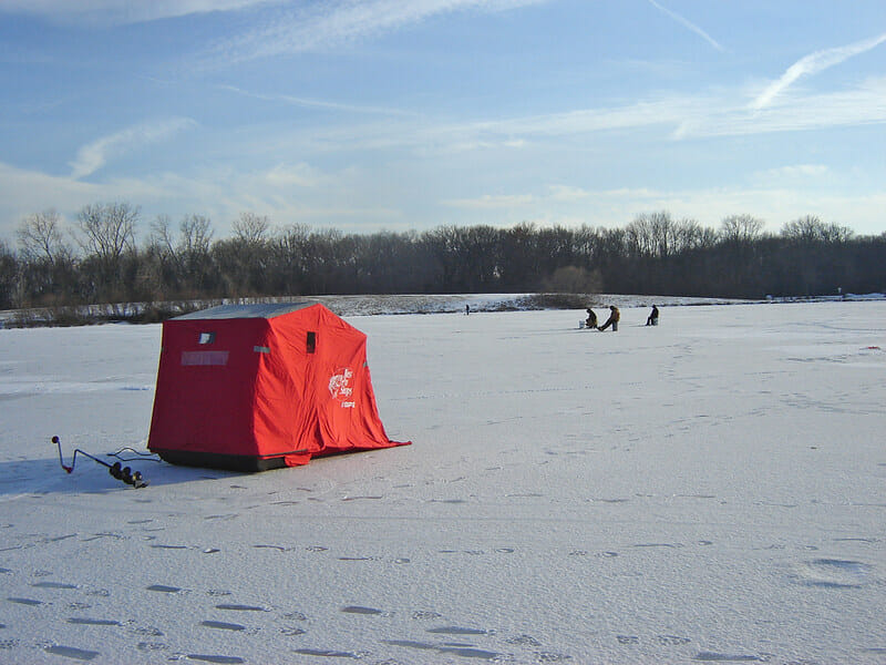 red ice fishing shanty on frozen lake