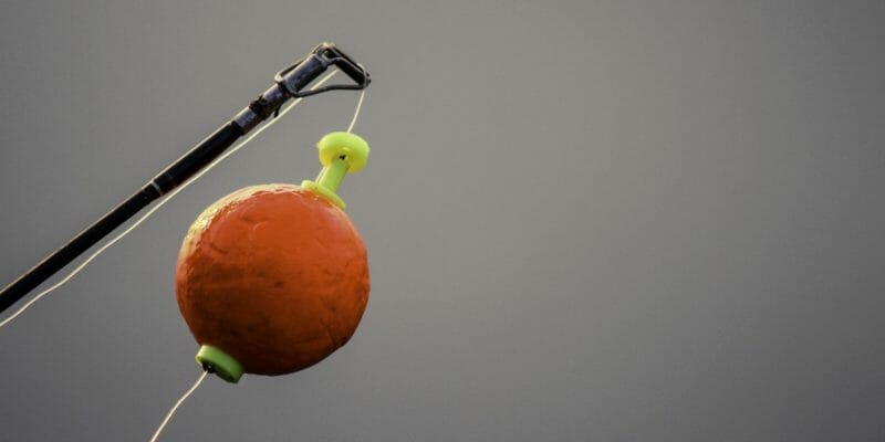 bright orange round fishing bobber on the end of fishing rod