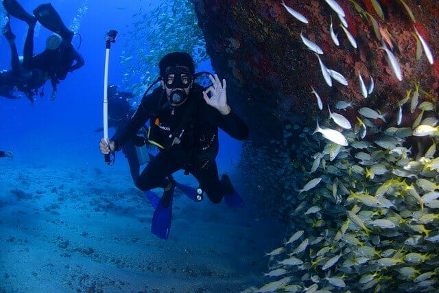 scuba diver in wetsuit giving the ok hand gesture