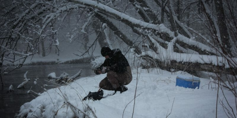 fly fisherman with waders and gloves near river
