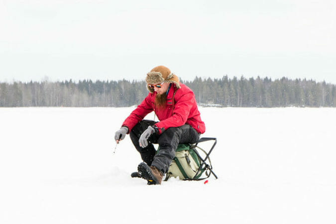 ice angler sitting on chair with small ice rod