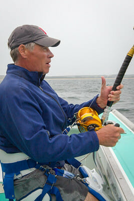 man tuna fishing with harness and heavy duty rod and reel