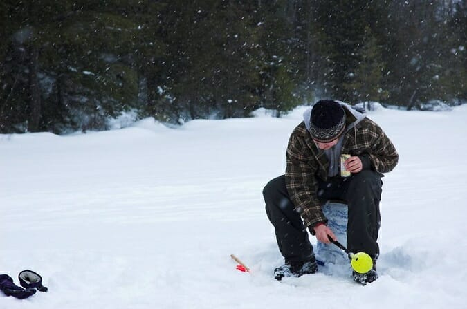 ice angler holding ice fishing scoop while sitting on bucket