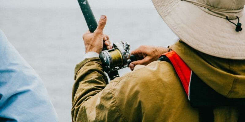 angler on a boat holding fishing rod
