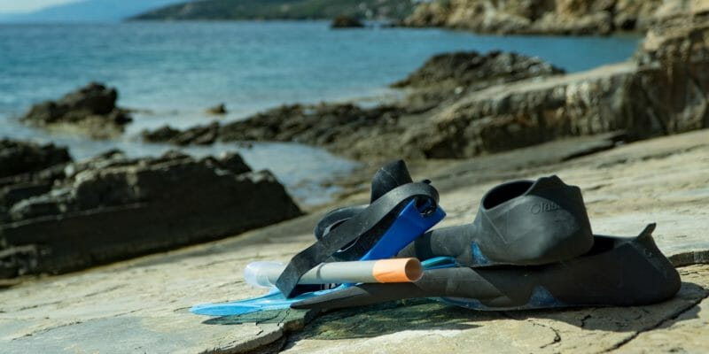 snorkeling gear on rocky beach