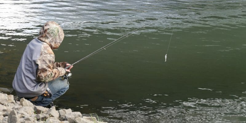angler with fishing rod near water