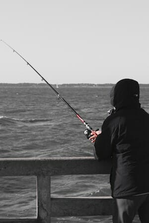 angler wearing fishing hoodie on pier