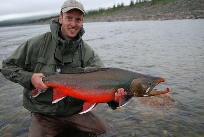 angler holding male arctic char