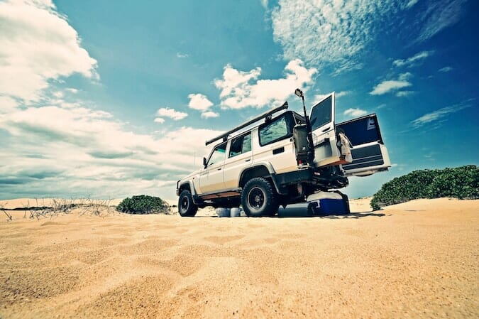 beach cooler on sand near jeep